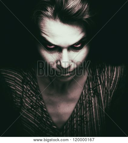 Face of scary woman with evil eyes in the dark