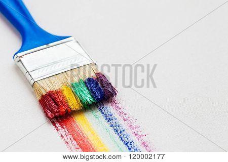 Paintbrush And Multicolor Rainbow Brush Strokes On White Artist Canvas