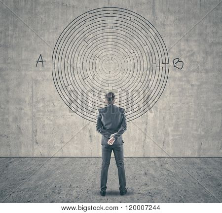 Businessman Looking At A Maze On Wall