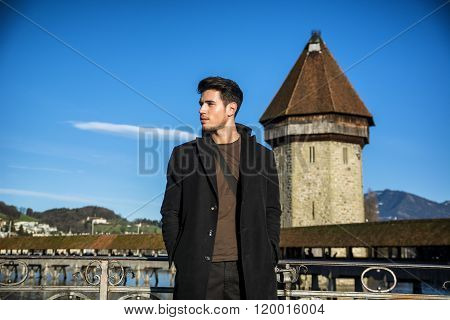 Man standing near metal fence in Lausanne