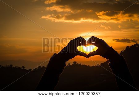 Silhouettes Hand Heart Shaped With Sunsets.
