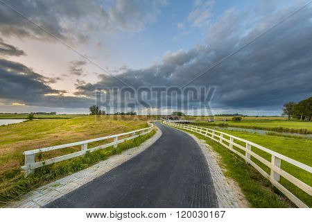 Curved Asphalt country road in dutch countryside of UNESCO world heritage area Reitdiepgebied with white fences leading to dam in the distance