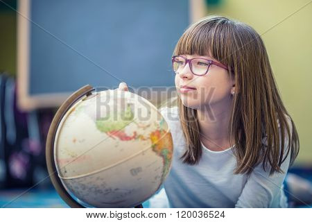Pretty little student girl studying geography with globe in a child's room