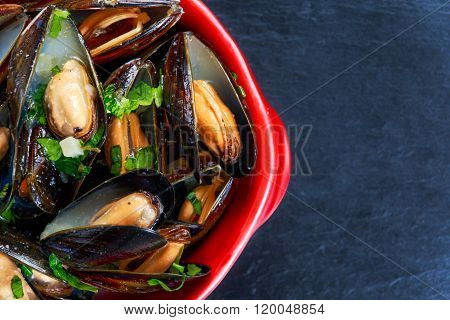 Mussels  garlic butter sauce in Red bowl.