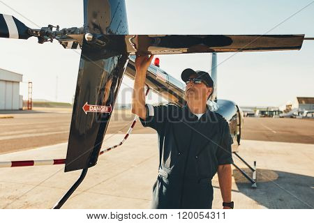 Male Pilot Examining Helicopter Tail Wing