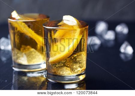 Alcohol cocktail with brandy whiskey lemon and ice in small glasses with copy space