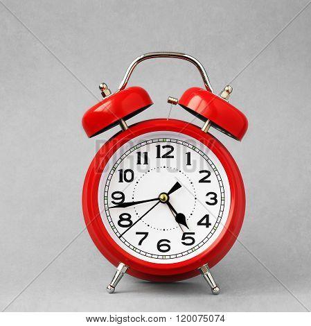Red Retro Alarm Clock  On A Grey Background.