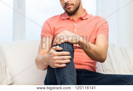 people, healthcare and problem concept - close up of young man suffering from pain in leg or knee at home