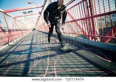Young skateboarder speed through the pedestrian walkway on Williamsburg Bridge NYC. Photographed in Feb 2016. poster