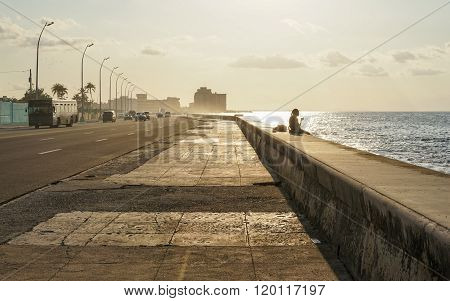 Silhouette Of Person Sitting On The Pier In Sun