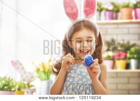 Happy easter! A beautiful child girl painting Easter eggs. Happy family preparing for Easter. Cute little child girl wearing bunny ears on Easter day.