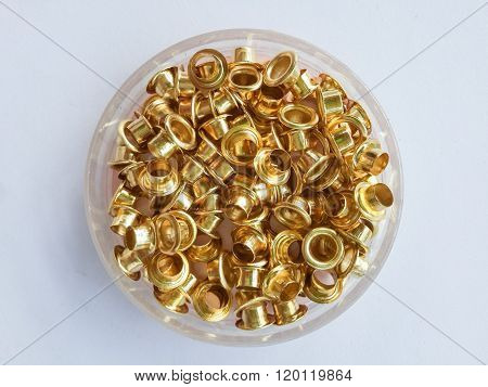 close up brass eyelets on white paper