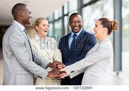 cheerful multiracial business team putting their hands together