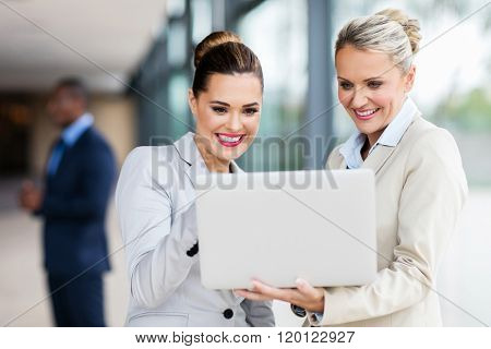 happy female colleagues working on laptop computer in modern office