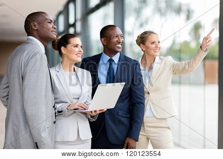 group of successful corporate workers discussing work in modern office