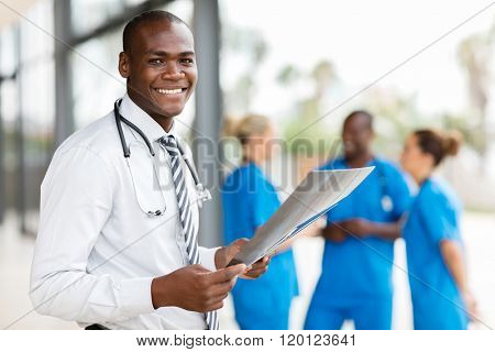 portrait of young african hospital doctor holding patient's x-ray