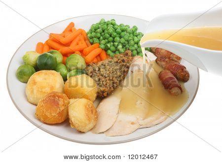 Roast chicken dinner with gravy being poured