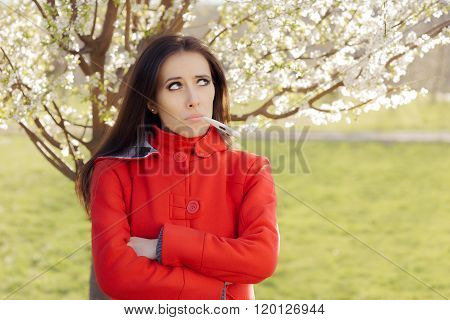 Sad Woman with Thermometer in Spring Blooming Decor