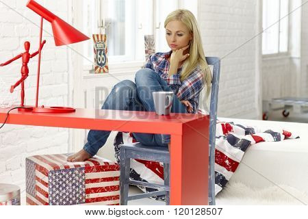 Thoughtful young woman sitting at desk at home in bad mood, looking down,