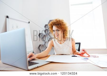 Cheerful curly redhead young woman cutting color paper and using laptop in office