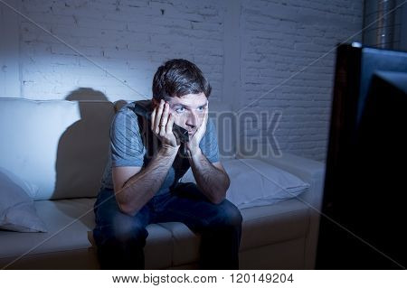 young attractive man at home lying on couch at living room watching tv holding remote control looking mesmerized and intense in television addict concept