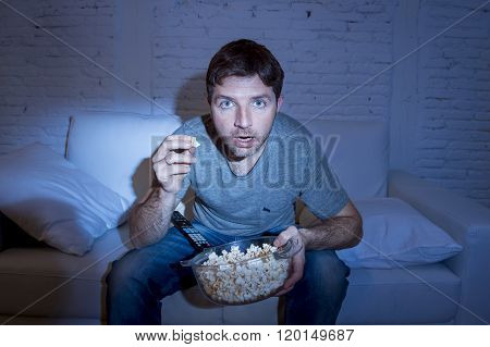 young attractive man at home lying on couch at living room watching tv holding popcorn bowl eating and looking mesmerized and intense concentration in television addict concept