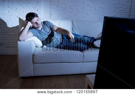 young attractive man at home lying on couch at living room watching tv holding remote control and changing channel or volume looking bored