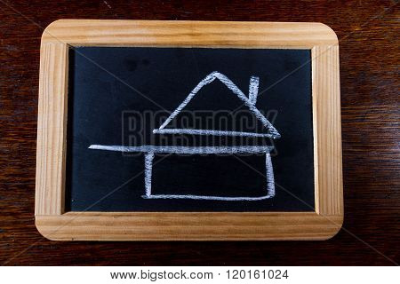 Blackboard with chalk symbol of home cooked food as drawn by child. Pan with roof.