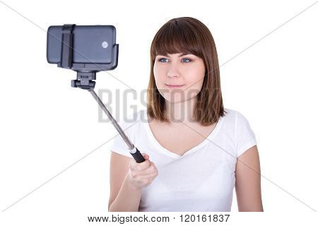 Happy Young Beautiful Woman Taking Photo On Smart Phone With Selfie Stick Isolated On White