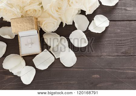 Ring Is Beside Of White Roses Flower Are On The Wooden Background