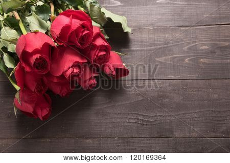 The Arrangement Of Red Roses Flower Are On The Wooden Background
