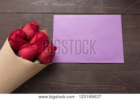 Red Roses Flower With The Card Are On The Wooden Background