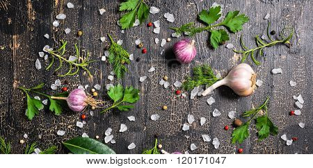 Top View Of Setting Garlic, Dry Peppers, Sea Salt, Different Greenery On Cracks Black Background, De