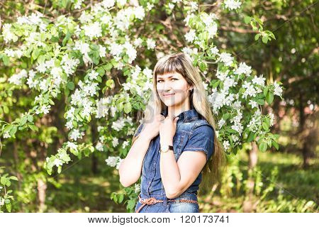 Young spring woman in blooming tree