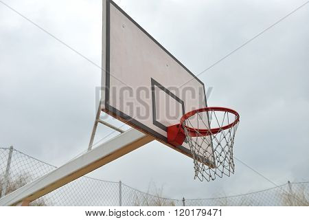 Basketball Board Under Cloudy Sky In A School Yard. Concept Of Kids Playing Outside. Team Game. Outd