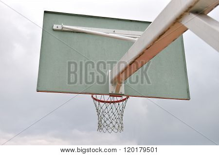 Behind Of Basketball Board Under Cloudy Sky In A School Yard. Concept Of Kids Playing Outside. Team
