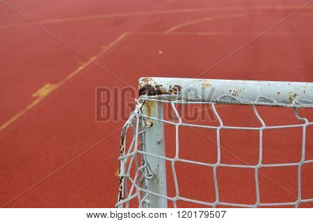 Detail Of Old And Rusty Gate Of Mini Football At A Soccer Field Made From Red And Green Granule Rubb