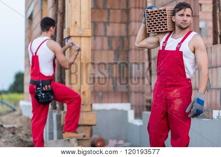 Image of two builders in workwear laboring hard poster