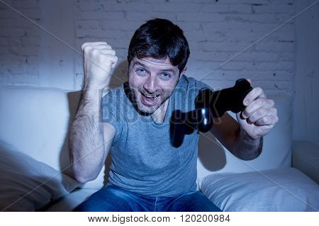 young excited man at home sitting on living room sofa playing video games using remote control joystick with freak intense face expression having fun in gaming addiction