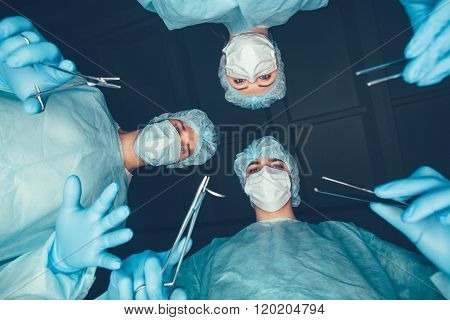 Medical team  hospital performing operation. Group of surgeon at work in operating theatre room. hea