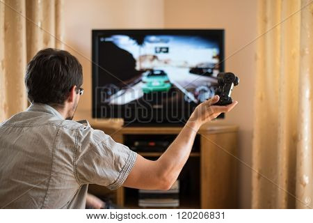 Man Playing Racing Video Game On Console In Home - Stock Photo