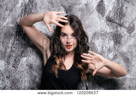 Beautiful fashion portrait of young woman. Studio shot on the dark abstract background.