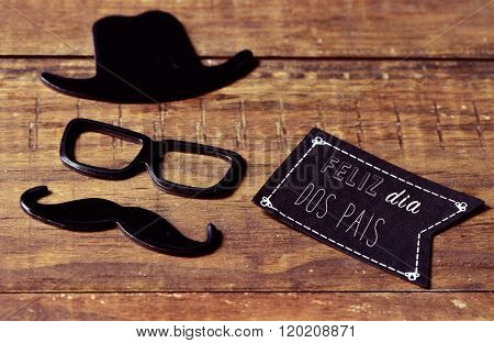 a black flag-shaped signboard with the text feliz dia dos pais, happy fathers day in portuguese, and a mustache, a pair of eyeglasses and a hat forming a man face on a wooden surface