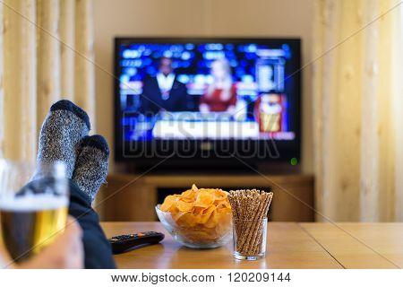 Man Watching Tv (television) News With Feet On Table