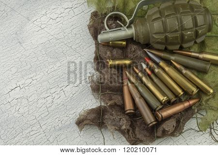 Different types of ammunition on a camouflage background. Possession of weapons.