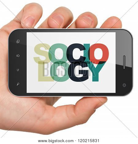Studying concept: Hand Holding Smartphone with Sociology on  display