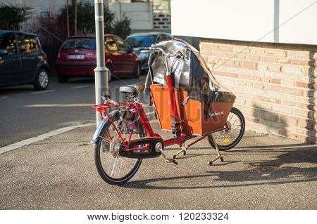 STRASBOURG FRANCE - DEC 25 2015: Cargo bike with protect tent parked on the street. The cargobike made by Bakfiets netherlands is a transport bicycle that's user friendly and ensures absolute cycling pleasure has a low instep and the centre of gravity is