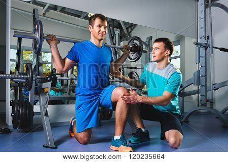 sport, fitness, teamwork, bodybuilding people concept - man and personal trainer with barbell flexin