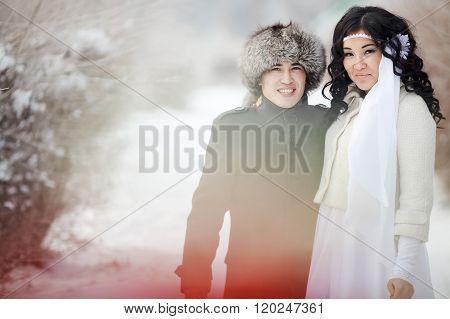 Winter wedding, exotic Asian couple newlyweds, groom in fur hat, bride wearing winter coat.