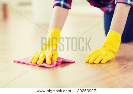 people, housework and housekeeping concept - close up of woman in rubber glover with cloth cleaning floor at home